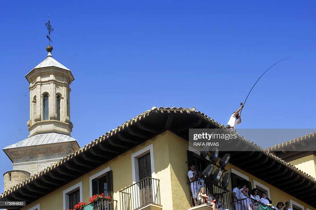 A man uses a fishing rod to hang a big Basque flag in front of Pamplona's Town Hall during the 'Chupinazo' to mark the start of the San Fermin Festival on July 6, 2013 in front of the Town Hall of Pamplona, northern Spain. Tens of thousands of people packed Pamplona's streets for a drunken kick-off to Spain's best-known fiesta: the nine-day San Fermin bull-running festival.