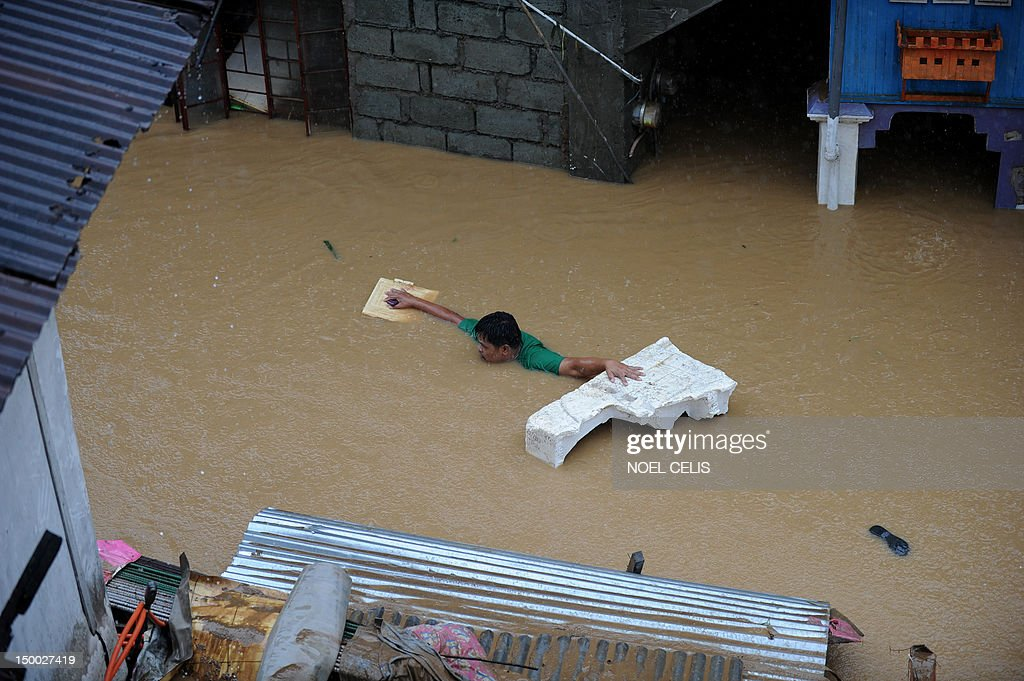 A man uses a flotation device to cross a flooded street near a river that overflowed caused by torrential rains in San Mateo, Rizal, suburban Manila on August 9, 2012. Philippine authorities appealed on August 9 for help in getting relief to two million people affected by deadly floods in and around the capital, warning that evacuation centres were overwhelmed.