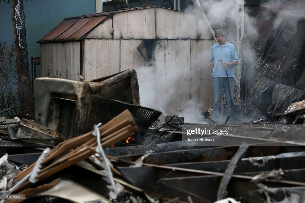 A man uses a garden hose cool hot spots from a fire at a mobile home park following a reported 6.0 earthquake on August 24, 2014 in Napa, California. A 6.0 earthquake rocked the San Francisco Bay Area shortly after 3:00 am on Sunday morning causing damage to buildings and sending at least 70 people to a hospital with non-life threatening injuries.