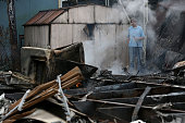 A man uses a garden hose cool hot spots from a fire at a mobile home park following a reported 60 earthquake on August 24 2014 in Napa California A...