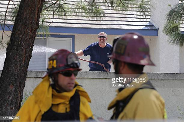 A man uses a garden hose to wet down his property as firefighters monitor the approaching wind driven Etiwanda fire April 30 2014 in Rancho Cucamonga...