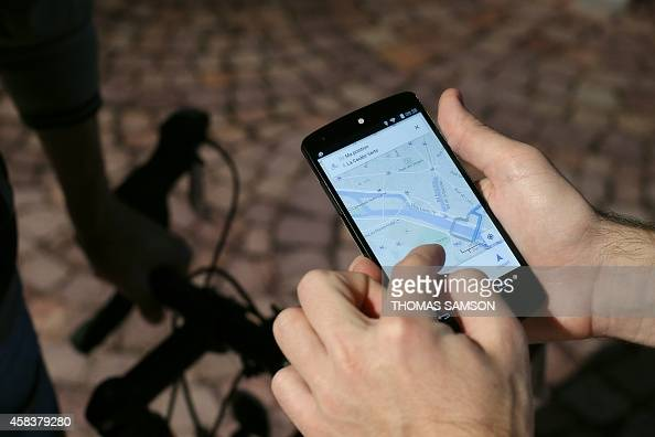 A man uses a GPS app on a smartphone during a Google promotion event at the City of Fashion and Design in Paris on November 4 2014 AFP PHOTO / THOMAS...