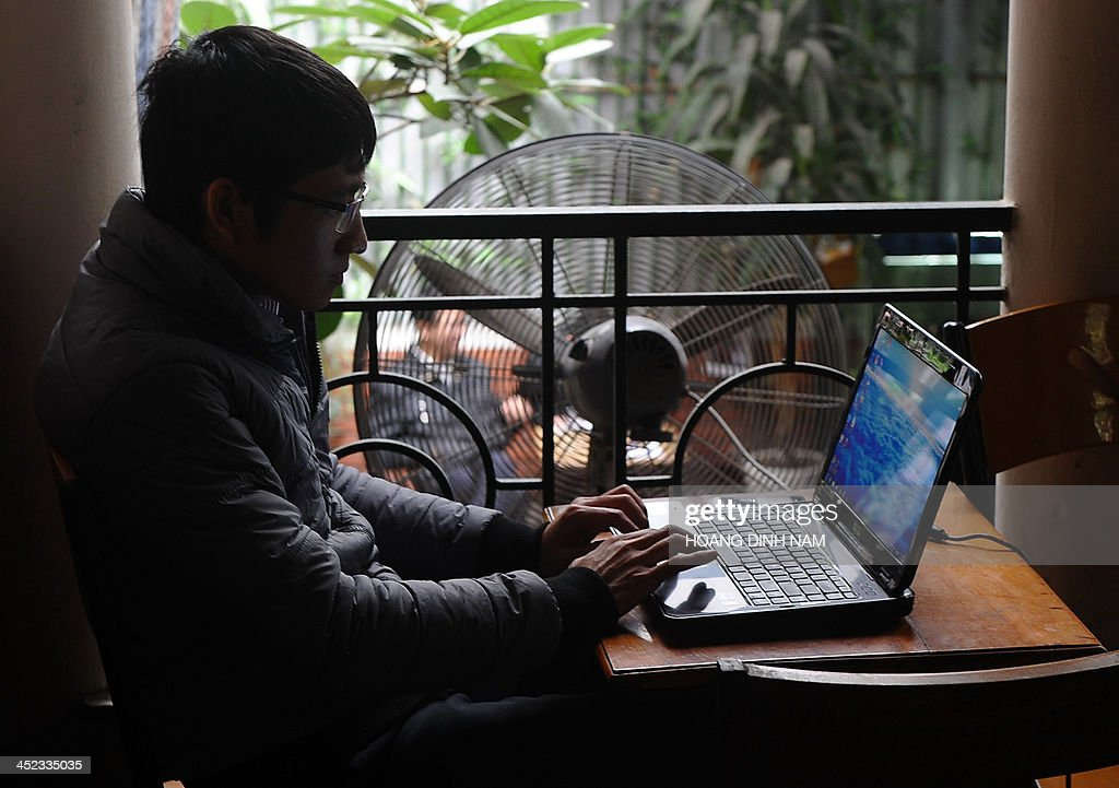 A man uses a laptop at a coffee shop in downtown Hanoi on November 28 2013 Vietnam has intensified a crackdown on online dissent with a new decree...