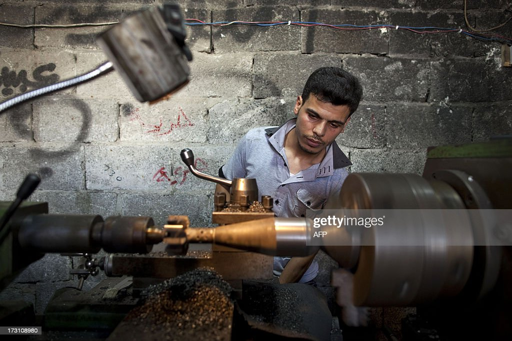 A man uses a lathe as he makes an improvised mortar shell to be used by rebel fighters at a factory in the city of Aleppo, Syria's commercial capital, on July 7, 2013. Syria's 27-month war between rebel forces and pro-government troops has killed more than 100,000 people, a monitoring group group estimates.