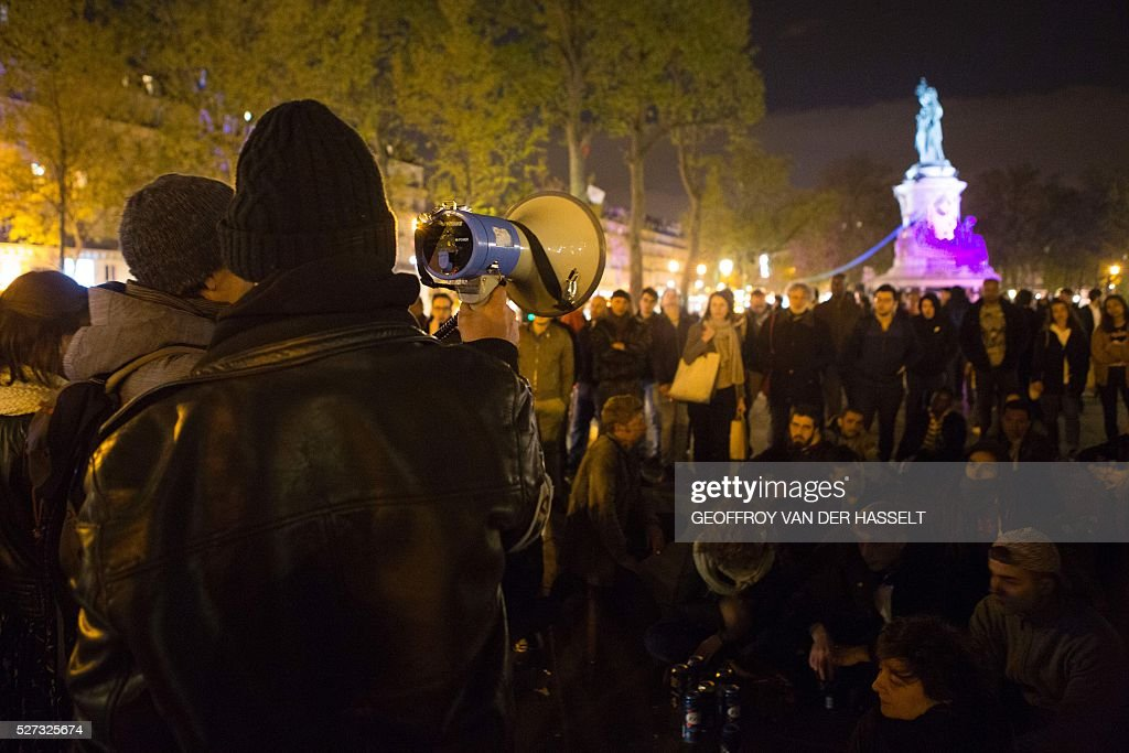 A man uses a megaphone to address people gathered for the 'Nuit debout' movement at Place de la Republique in Paris on May 2, 2016, after restrictions were put in place preventing organizers from using speakers after 10pm. A wave of protests over planned labour reforms inspired a new youth movement dubbed 'Nuit Debout' (Up All Night) that kicked off on March 31. It has since embraced a range of grievances, spreading from Paris to several other cities. / AFP / Geoffroy Van der Hasselt