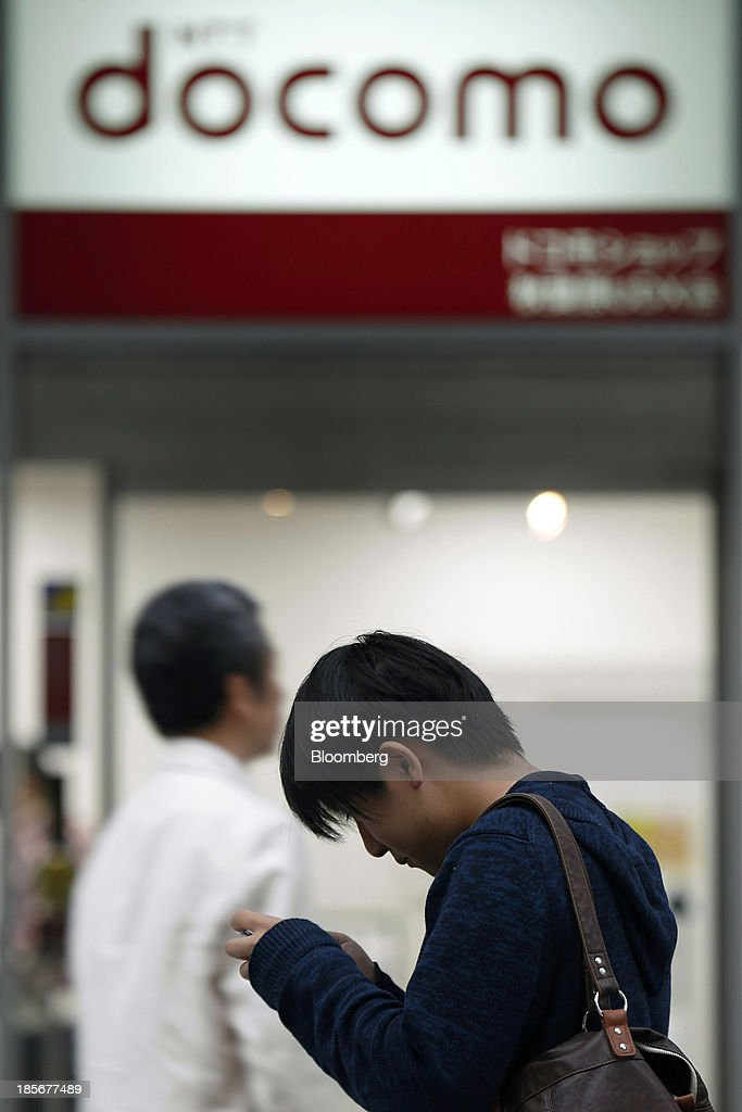 A man uses a mobile device in front of an NTT Docomo Inc. store in Tokyo, Japan, on Wednesday, Oct. 23, 2013. DoCoMo, Japan's largest mobile phone carrier, is scheduled to release earnings results on Oct. 25. Photographer: Kiyoshi Ota/Bloomberg via Getty Images