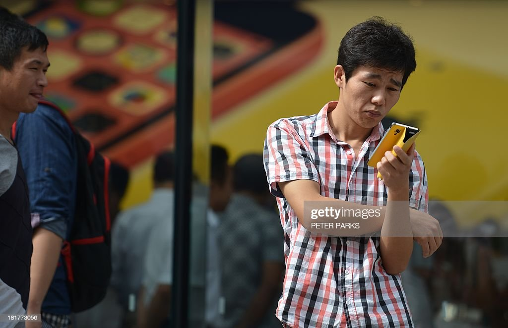 A man uses a mobile device outside a store in Shanghai on September 25 2013 China will open its first free trade zone in an ambitious effort to...