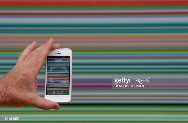 A man uses a mobile device to take pictures of the work 'Strip ' by German visual artist Gerhard Richter during a preview of the show 'Gerhard...