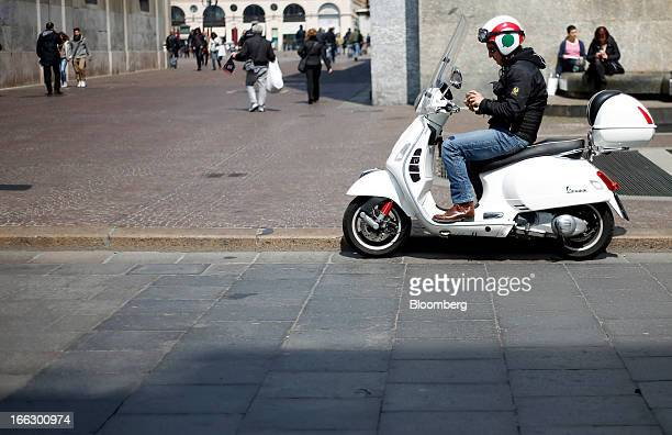 A man uses a mobile handset as he sits on a Vespa scooter produced by Piaggio C SpA in Turin Italy on Wednesday April 10 2013 Italian Prime Minister...