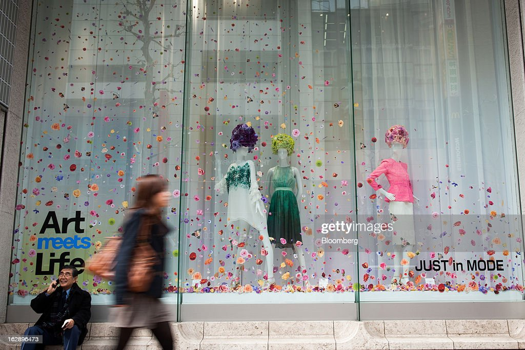 A man uses a mobile phone as a woman walks past a clothing store in the area of Shibuya in Tokyo, Japan, on Friday, March 1, 2013. Japan's consumer prices fell for the eighth time in nine months, highlighting the challenges facing the Bank of Japan in reaching a 2 percent inflation target. Photographer: Noriko Hayashi/Bloomberg via Getty Images