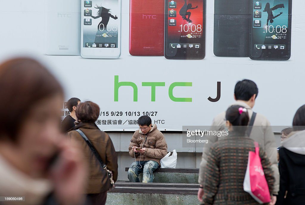 A man uses a mobile phone as he sits in front of an advertisement for HTC Corp.'s J smartphone in Taipei, Taiwan, on Sunday, Jan. 6, 2013. HTC is scheduled to release fourth-quarter earnings on Jan. 7. Photographer: Maurice Tsai/Bloomberg via Getty Images