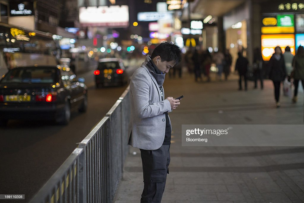 A man uses a mobile phone as he stands by the side of a road in Hong Kong, China, on Friday, Jan. 4, 2013. Chief Executive Leung Chun-ying, who has been buffeted by student protests and low popularity since taking office on July 1, has pledged to tackle Asia's biggest wealth gap as the division between poor and rich widened to its worst level since at least 1971. Photographer: Jerome Favre/Bloomberg via Getty Images