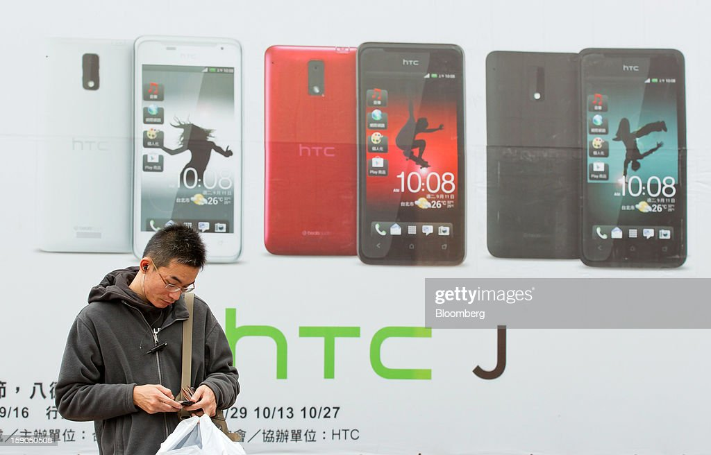 A man uses a mobile phone as he stands in front of an advertisement for HTC Corp.'s J smartphone in Taipei, Taiwan, on Sunday, Jan. 6, 2013. HTC is scheduled to release fourth-quarter earnings on Jan. 7. Photographer: Maurice Tsai/Bloomberg via Getty Images