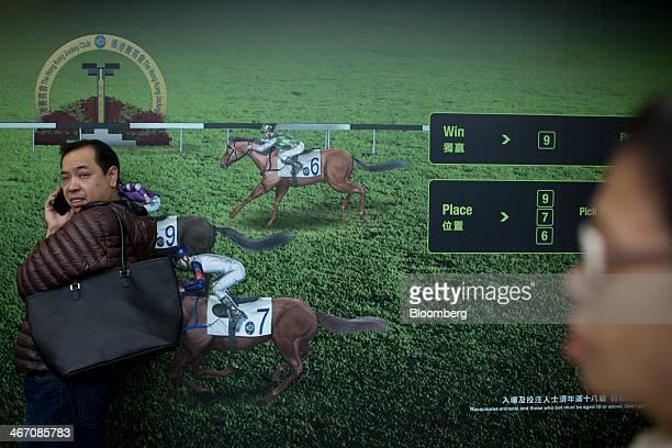A man uses a mobile phone at the Hong Kong Jockey Club Happy Valley race course in Hong Kong China on Wednesday Feb 5 2014 The Hong Kong Jockey Club...