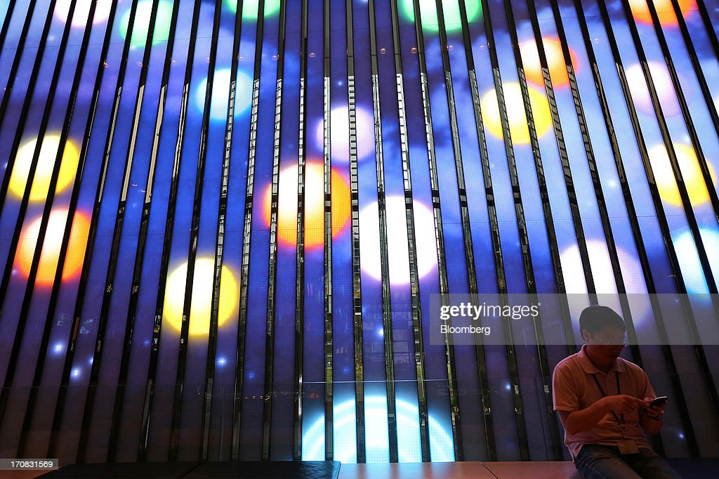 A man uses a mobile phone in front of a light wall at the Samsung Electronics Co. d'light store in Seoul, South Korea, on Tuesday, June 18, 2013. Facebook Inc. Chief Executive Officer Mark Zuckerberg, seeking to boost advertising sales from mobile devices, discussed potential partnerships with Samsung Electronics Co., according to the head of the South Korean companys handset division. Photographer: SeongJoon Cho/Bloomberg via Getty Images