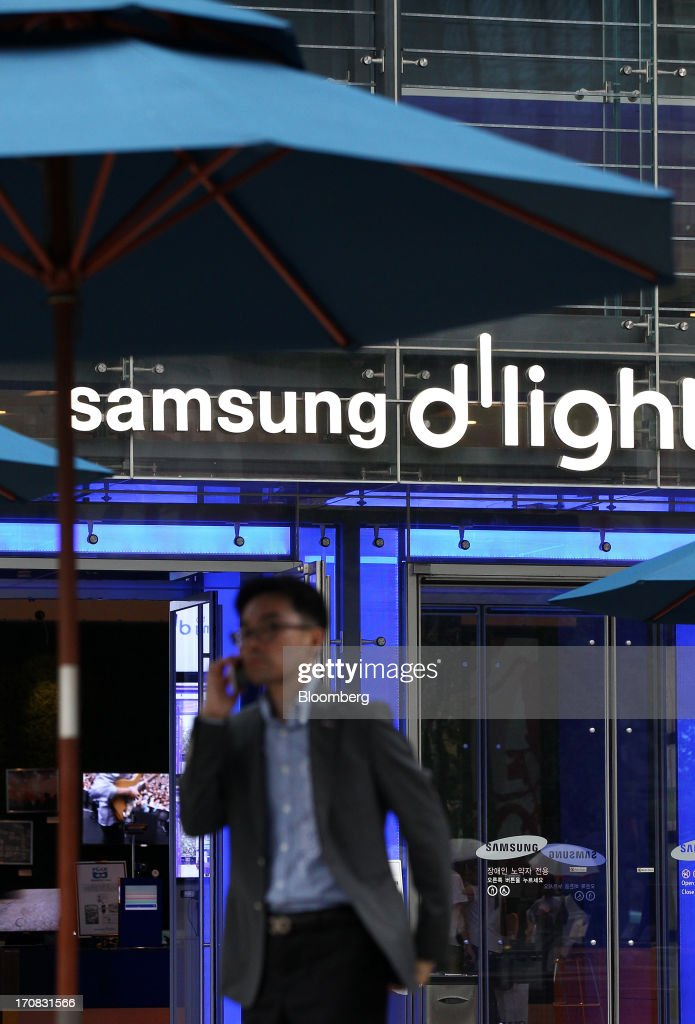 A man uses a mobile phone in front of the Samsung Electronics Co. d'light store in Seoul, South Korea, on Tuesday, June 18, 2013. Facebook Inc. Chief Executive Officer Mark Zuckerberg, seeking to boost advertising sales from mobile devices, discussed potential partnerships with Samsung Electronics Co., according to the head of the South Korean companys handset division. Photographer: SeongJoon Cho/Bloomberg via Getty Images