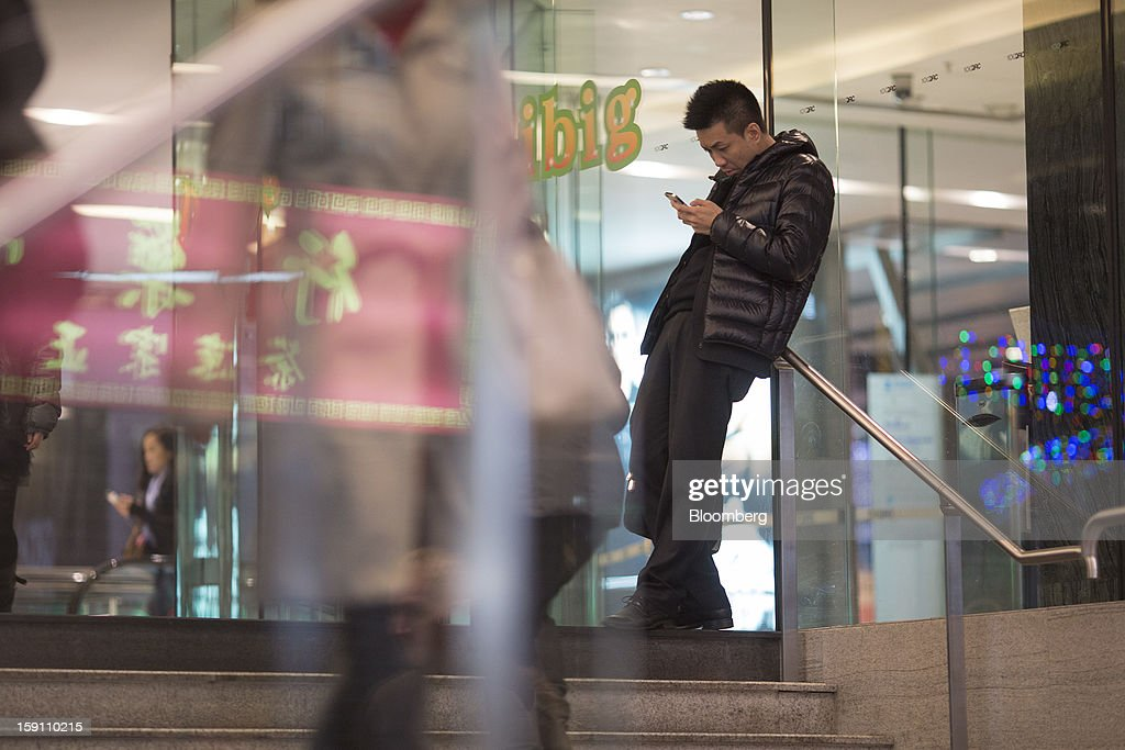 A man uses a mobile phone in Hong Kong, China, on Friday, Jan. 4, 2013. Chief Executive Leung Chun-ying, who has been buffeted by student protests and low popularity since taking office on July 1, has pledged to tackle Asia's biggest wealth gap as the division between poor and rich widened to its worst level since at least 1971. Photographer: Jerome Favre/Bloomberg via Getty Images