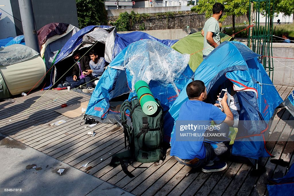 A man uses a mobile phone next to his tent in a makeshift camp in Paris on May 27, 2016. The population of the camp come mostly from Sudan and Afghanistan. The refugee crisis gripping Europe is a problem that the whole world must deal with, G7 leaders said May 27, as it called for beefed-up efforts to tackle the root causes of mass migration. / AFP / MATTHIEU