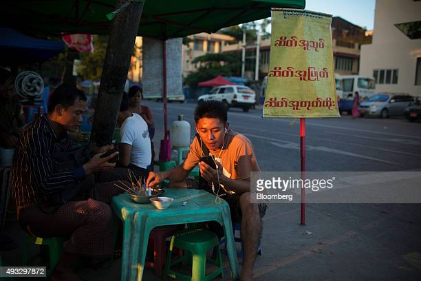 A man uses a mobile phone while sitting at a roadside restaurant in Yangon Myanmar on Thursday Oct 15 2015 Myanmar's government signed a ceasefire...