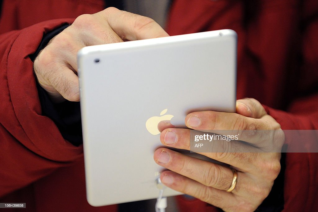 A man uses a new iPad mini during the opening of a new Apple store on November 15, 2012 in Saint-Herblain, western France. AFP PHOTO / JEAN-SEBASTIEN EVRARD