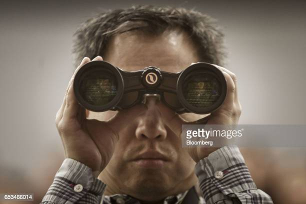 A man uses a pair of binoculars during the closing ceremony of the National People's Congress in Beijing China on Wednesday March 15 2017 China's...