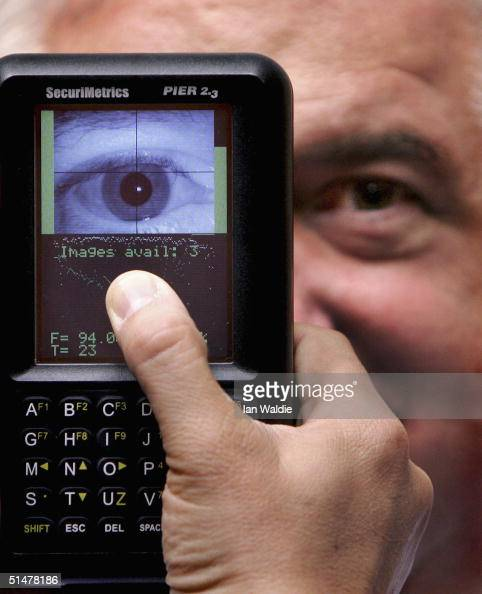 A man uses a portable iris recognition scanner during the Biometrics 2004 exhibition and conference October 14 2004 in London The conference will...