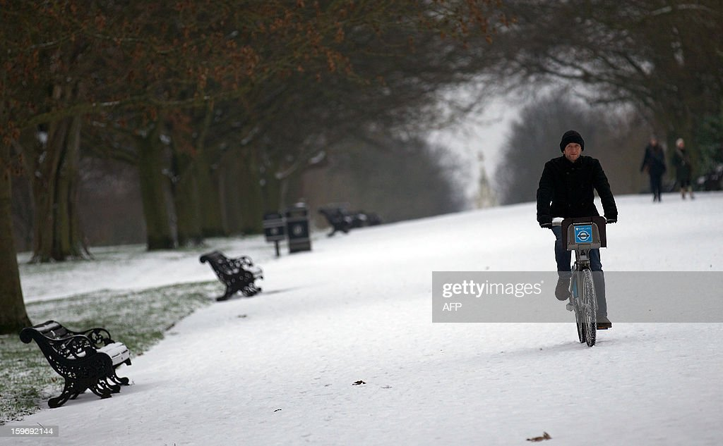 A man uses a rental bicycle as he rides through in Regent's Park after snowfall in central London on January 18, 2013. Snow swept across Britain, forcing airports to cancel hundreds of flights and more than 3,000 schools to close.