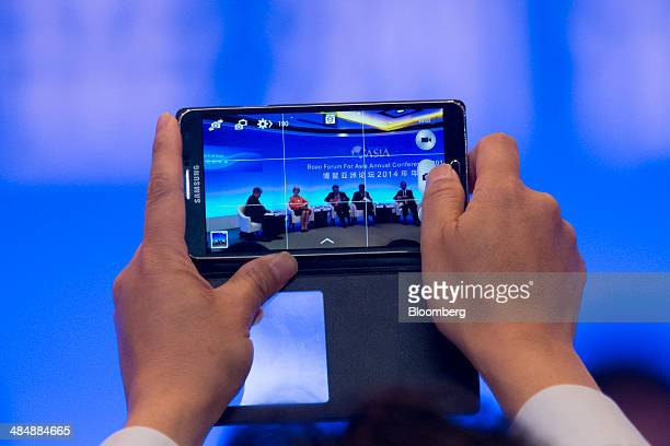 A man uses a Samsung Electronics Co mobile device to take a photograph during a session at the Boao Forum for Asia in Boao Hainan China on Thursday...