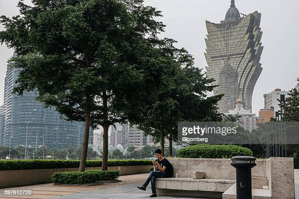 A man uses a smartphone as Casino Grand Lisboa operated by SJM Holdings Ltd right stand in the distance in Macau China on Sunday Aug 28 2016 Macau is...