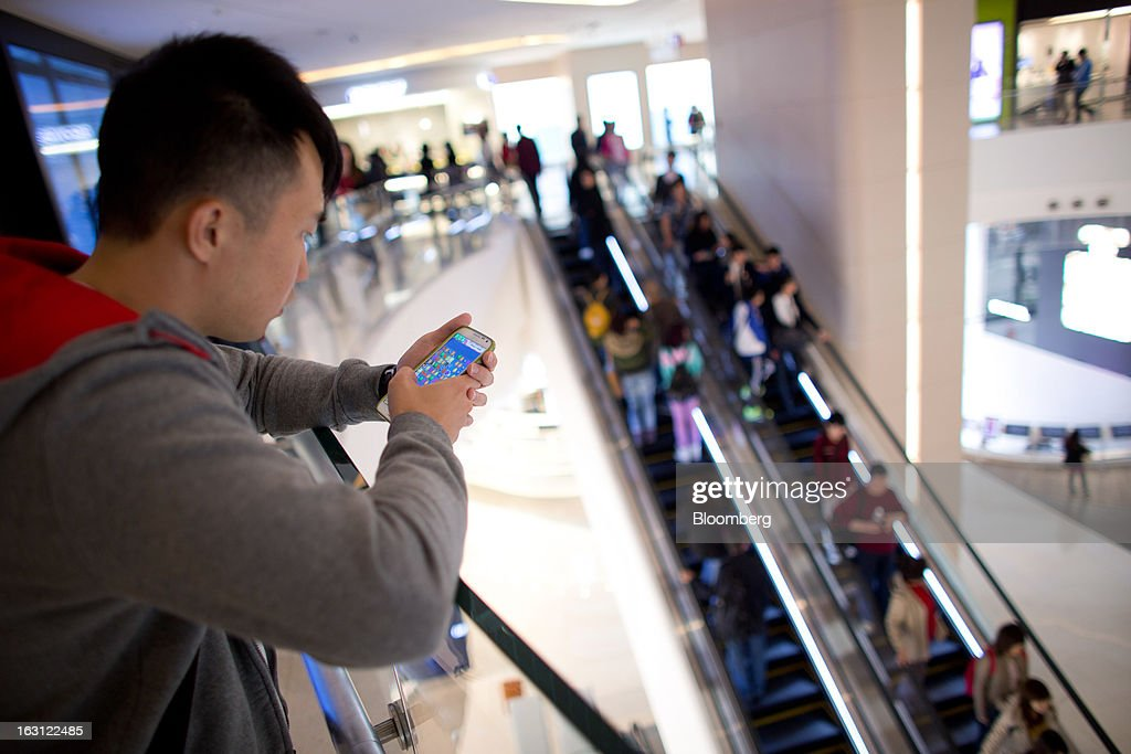 A man uses a smartphone as customers ride on escalators at Hysan Development Co.'s Hysan Place mall in the Causeway Bay district of Hong Kong, China, on Monday, March 4, 2013. Hysan is scheduled to release earnings on March 6. Photographer: Lam Yik Fei/Bloomberg via Getty Images