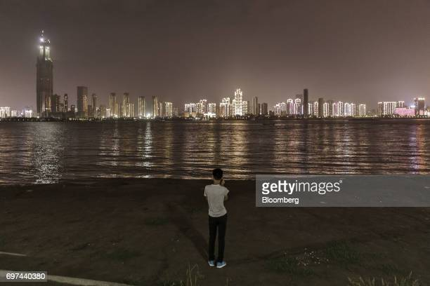 A man uses a smartphone as he looks out at illuminated buildings standing along the Yangtze River at night in Wuhan China on Tuesday June 13 2017...