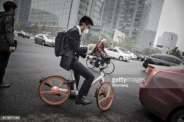 A man uses a smartphone as he rides a Beijing Mobike Technology Co bicycle through an intersection in Beijing China on Wednesday Oct 19 2016 This...