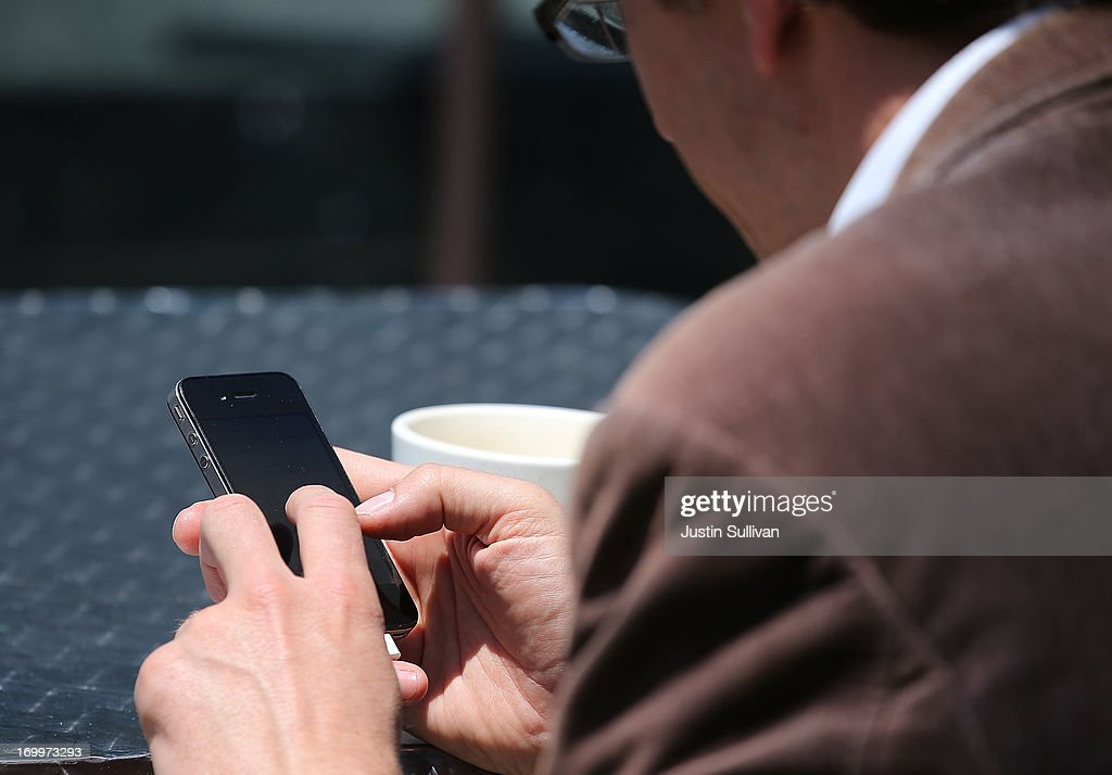 A man uses a smartphone as he sits in Union Square on June 5, 2013 in San Francisco, California. According to a study by the Pew Internet & American Life Project, over half of American adults, or 56 percent, have smartphones, up from 35 percent two years ago.