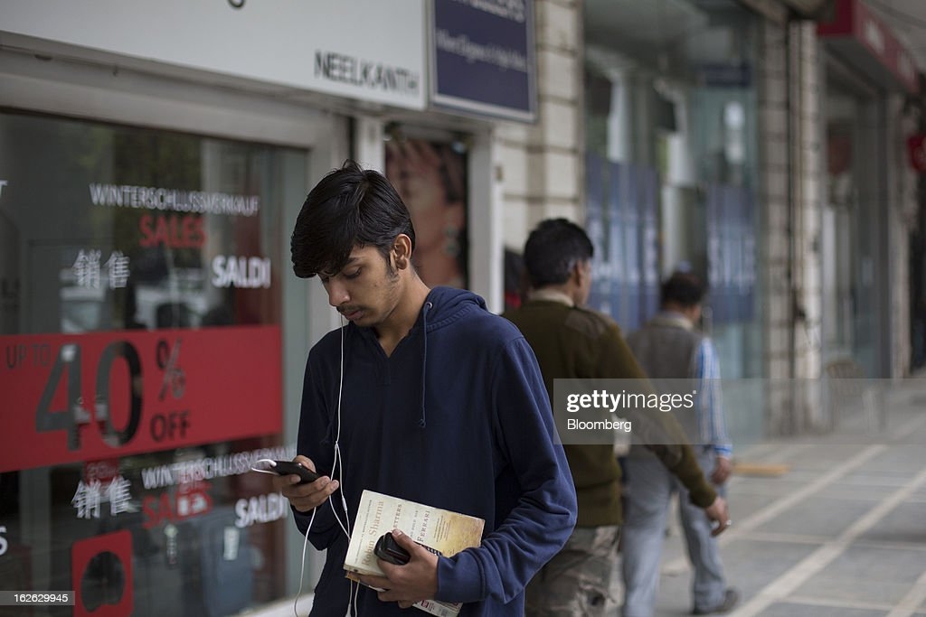 A man uses a smartphone as he walks through Connaught Place in New Delhi, India, on Saturday, Feb. 23, 2013. Finance Minister Palaniappan Chidambaram, who will present his annual budget to parliament on Feb. 28, will seek to narrow the shortfall to 4.8 percent of gross domestic product in the year starting April, from this year's goal of 5.3 percent, according to a Bloomberg survey of analysts and investors. Photographer: Brent Lewin/Bloomberg via Getty Images