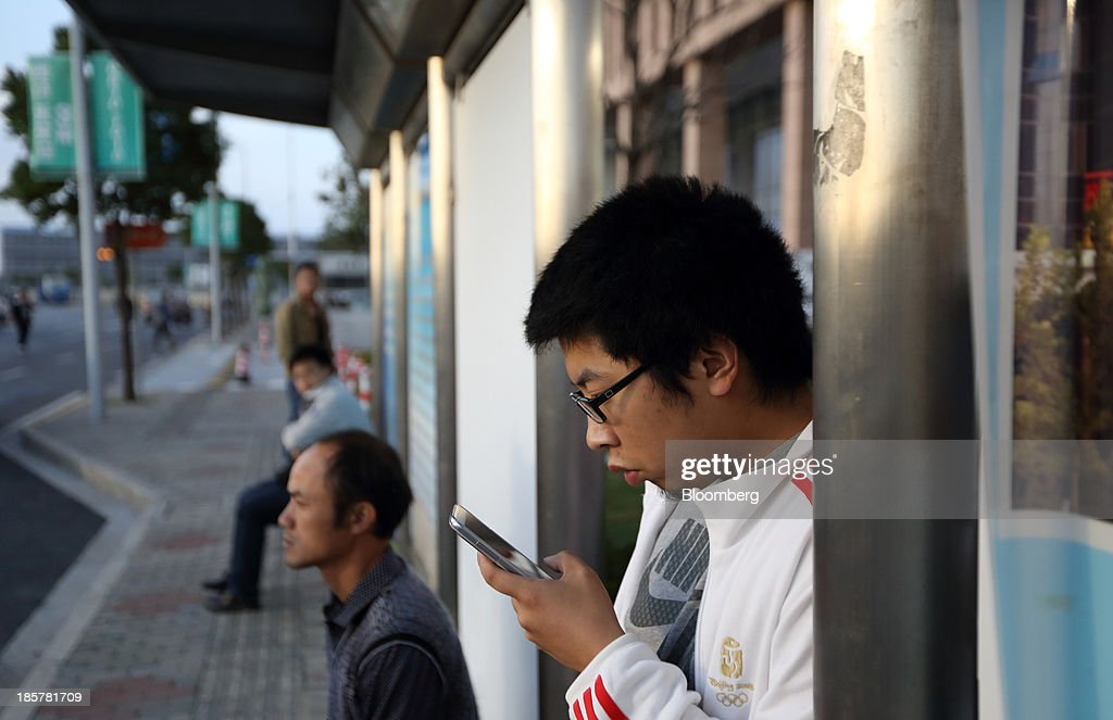 A man uses a smartphone at a bus stop in China (Shanghai) Pilot Free Trade Zone's Pudong free trade zone in Shanghai, China, on Thursday, Oct. 24, 2013. The area is a testing ground for free-market policies that Premier Li Keqiang has signaled he may later implement more broadly in the world's second-largest economy. Photographer: Tomohiro Ohsumi/Bloomberg via Getty Images