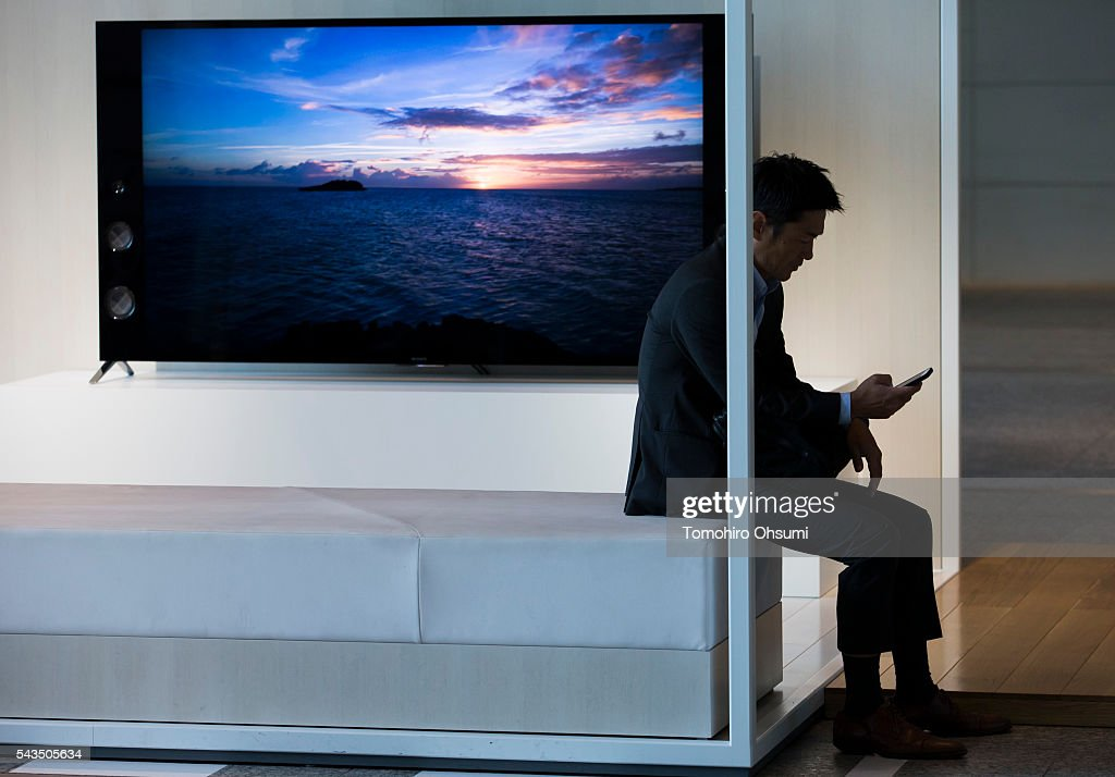 A man uses a smartphone in front of a Sony Corp. television at the company's headquarters on June 29, 2016 in Tokyo, Japan. Sony announced its mid-range business strategy plan from FY2015 through 2017 today.