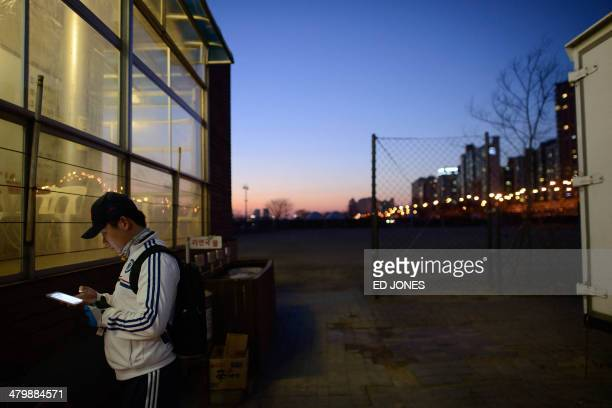 A man uses a smartphone in Seoul on March 21 2014 South Korea already one of the most wired countries on earth announced in January 2014 a 16...