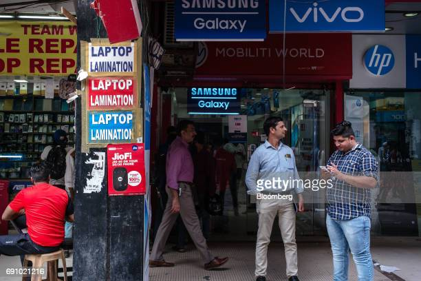 A man uses a smartphone outside a store selling Samsung Electronics Co mobile phones at the Nehru Place IT Market in New Delhi India on Tuesday May...