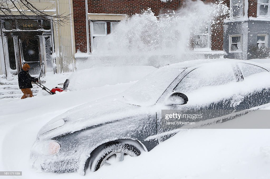 A man uses a snow blower on the sidewalk in the Brighton neighborhood on February 9, 2013 in Boston, Massachusetts. The powerful storm has knocked out power to 650,000 and dumped more than two feet of snow in parts of New England.
