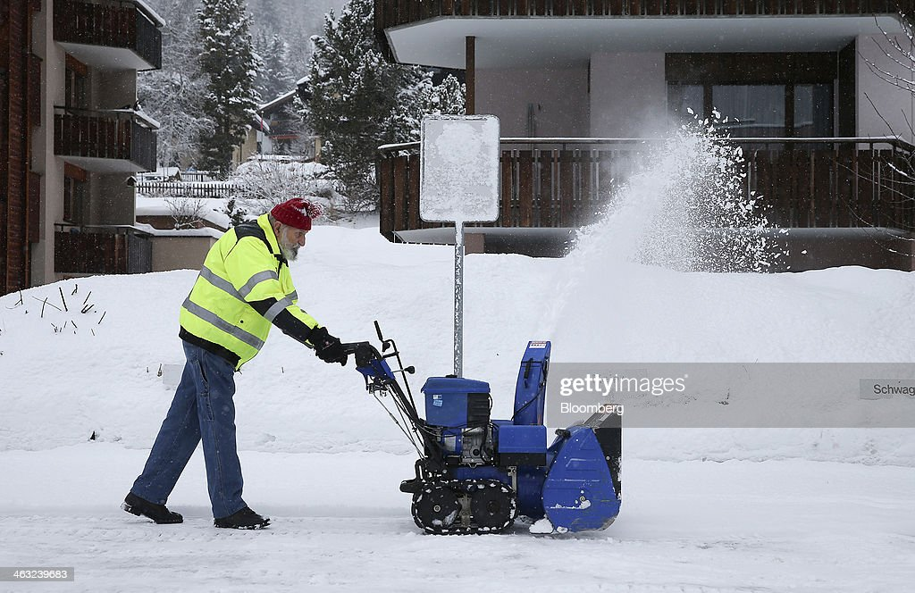 A man uses a snow blower to clear fresh snow near residential properties in Davos, Switzerland, on Friday, Jan. 17, 2014. Next week the business elite will gather in the Swiss Alps for the 44th annual meeting of the World Economic Forum (WEF) in Davos for the five day event which runs from Jan. 22-25. Photographer: Simon Dawson/Bloomberg via Getty Images