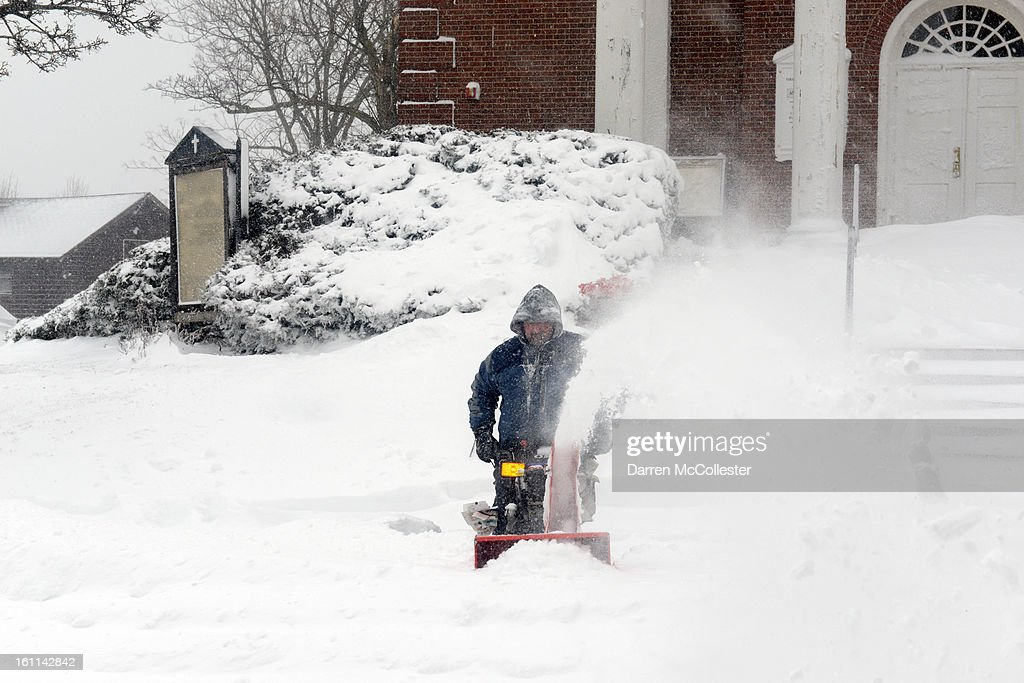A man uses a snow blower to clear the sidewalk in Winthrop Center February 9, 2013 in Winthrop, Massachusetts. An overnight blizzard left one to two feet of snow in some areas, and coastal flooding is expected as the storm lingers into the day.