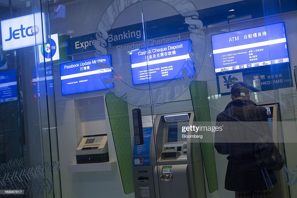A man uses a Standard Chartered Plc automated teller machine (ATM) in one of the company's bank branches in Hong Kong, China, on Saturday, March 2, 2013. Standard Chartered is scheduled to release annual results on March 5. Photographer: Jerome Favre/Bloomberg via Getty Images