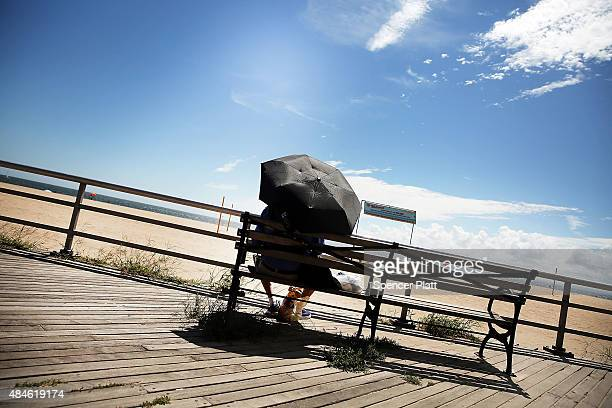 A man uses a sun umbrella along the boardwalk at Brighton Beach in Brooklyn on August 20 2015 in New York City The National Oceanic and Atmospheric...