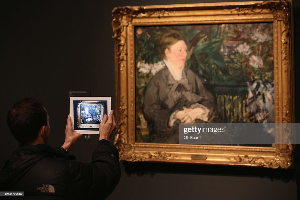 A man uses a tablet computer to take a photograph of a painting by Edouard Manet entitled 'Mme Manet in the Conservatory' in the Royal Academy of Arts on January 22, 2013 in London, England. The painting features in the Royal Academy's new exhibition 'Manet: Portraying Life' which displays over 50 paintings spanning his career. The exhibition open to the general public on January 26, 2013 and runs until April 14, 2013.