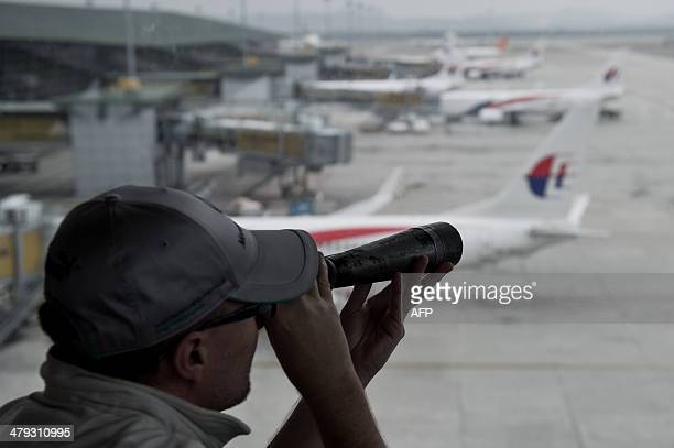 A man uses a telescope to look out over the planes on the tarmac at Kuala Lumpur International Airport in Sepang on March 18 2014 The last words from...