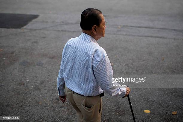 A man uses a walking cane as he walks through Lumphini Park in Bangkok Thailand on Sunday March 15 2015 Almost a third of Thailand's population will...