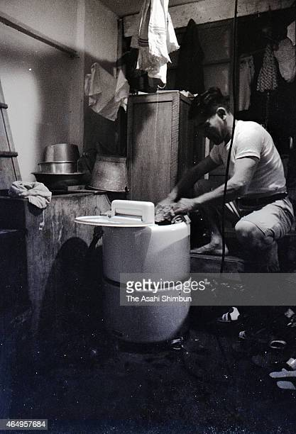 A man uses a washing machine at the concrete apartment at Hashima on August 12 1956 in Takashima Nagasaki Japan The coal mining island is also known...