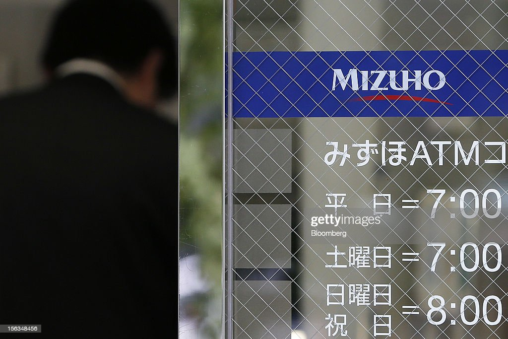 A man uses an automated teller machine (ATM) at a Mizuho Bank Ltd. branch in Tokyo, Japan, on Tuesday, Nov. 13, 2012. Mizuho Financial Group Inc. is scheduled to announce first-half earnings results on Nov. 14. Photographer: Kiyoshi Ota/Bloomberg via Getty Images