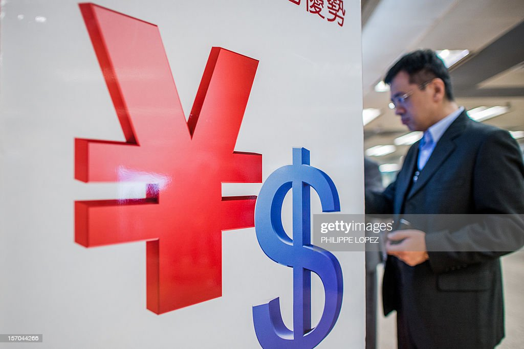 A man uses an automatic teller machine (ATM) next to Chinese yuan (L) and US dollar symbols in Hong Kong on November 28, 2012. The US Treasury on November 27 again stopped short of labelling China a currency manipulator, noting gains in the value of the yuan, but said the currency remains 'significantly undervalued.' AFP PHOTO / Philippe Lopez