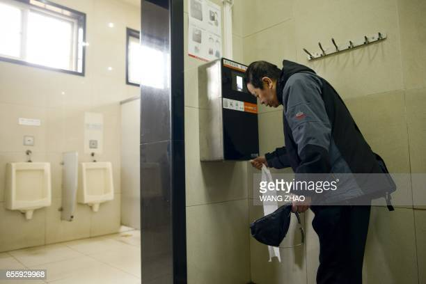 A man uses an automatic toilet paper dispenser that uses facial recognition technology at a public toilet at the Temple of Heaven in Beijing on March...